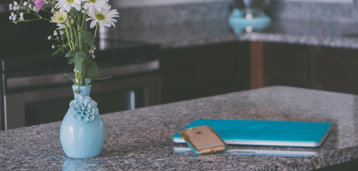 Kitchen counter island with a flower vase, iPhone, and notepad