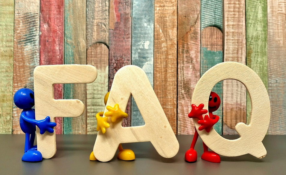 Toy figurines holding FAQ letters