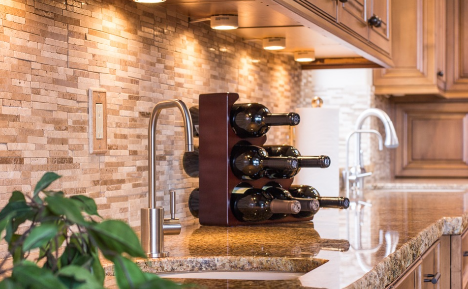 Glossy kitchen countertop with a rack of wine